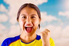 Jeune femme d'ecuadorian portant l'appareil-photo debout de revêtement de marathon de chemise officielle du football, langage du  Photo stock
