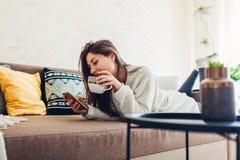 Jeune femme d?tendant dans le salon utilisant le smartphone et le caf? potable D?cor int?rieur photos stock