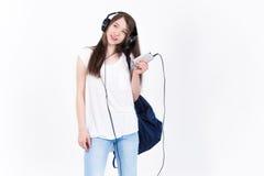 Jeune femme dans des écouteurs chantant des chansons sur un fond blanc Photographie stock libre de droits