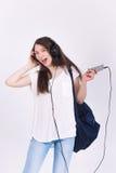 Jeune femme dans des écouteurs chantant des chansons sur un fond blanc Image stock