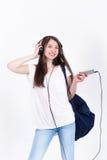 Jeune femme dans des écouteurs chantant des chansons sur un fond blanc Photo libre de droits