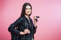 Jeune femme dans des clés de veste en cuir, de sac et de voiture Photographie stock libre de droits