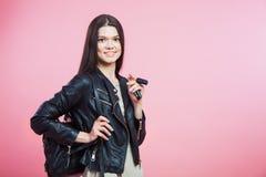 Jeune femme dans des clés de veste en cuir, de sac et de voiture Photo stock