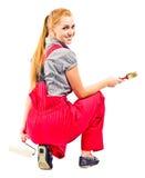 Jeune femme dans des combinaisons rouges avec des outils de peinture images libres de droits