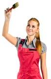Jeune femme dans des combinaisons rouges avec la brosse photo stock