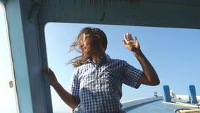Jeune femme dans des danses de lunettes de soleil sur un yacht, contre le contexte du coucher de soleil Appréciez une croisière d banque de vidéos