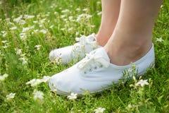 Jeune femme dans des espadrilles classiques blanches se tenant dans l'herbe sur le pré de ressort Images stock