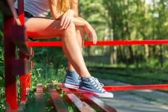 Jeune femme dans des espadrilles sur un arrêt d'autobus Image libre de droits