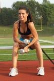 Jeune femme dans des haltères de fixation de soutien-gorge de sports sur le banc Photographie stock libre de droits