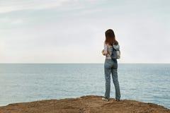 Jeune femme dans des jeans, dans le dessus et des espadrilles rayés sur la plage b Photographie stock