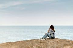 Jeune femme dans des jeans, dans le dessus et des espadrilles rayés sur la plage b Image stock