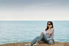 Jeune femme dans des jeans, dans le dessus et des espadrilles rayés sur la plage b Image libre de droits