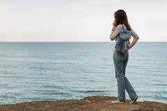 Jeune femme dans des jeans, dans le dessus et des espadrilles rayés sur la plage b Photo stock