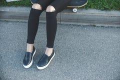 Jeune femme dans des jeans, espadrilles se reposant au sol à côté de sa planche à roulettes dehors Photographie stock