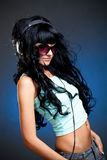 Jeune femme dans des lunettes de soleil avec des écouteurs Photographie stock