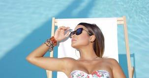 Jeune femme dans des lunettes de soleil détendant au soleil banque de vidéos