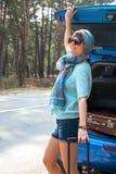 Jeune femme dans des lunettes de soleil près de la voiture avec une valise Photos stock