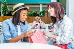 Jeune femme dans des lunettes de soleil regardant les amis de sourire avec le panier Photos libres de droits