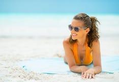 Jeune femme dans des lunettes de soleil s'étendant sur la côte Photos libres de droits