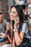 Jeune femme dans des lunettes parlant sur le smartphone et les amis s'asseyant derrière Photo stock