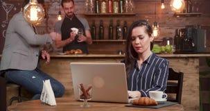 Jeune femme dans des rires d'un café tout en composant un texte sur son carnet banque de vidéos