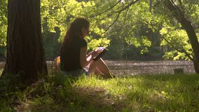 Jeune femme dans des utilisations smartphone et comprimé de parc clips vidéos