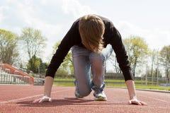 Jeune femme dans des vêtements sport sur une voie de tartan Photographie stock