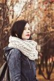Jeune femme dans l'écharpe chaude avec le rouge à lèvres rouge en parc d'automne, images libres de droits