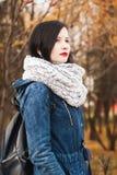 Jeune femme dans l'écharpe chaude avec le rouge à lèvres rouge en parc d'automne, image libre de droits