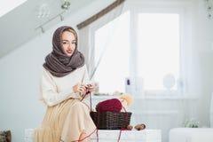 Jeune femme dans l'écharpe tricotée à la main chaude d'avançon à la maison Photo libre de droits