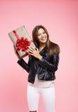 Jeune femme dans l'équipement frais tenant le cadeau d'anniversaire regardant directement Images libres de droits