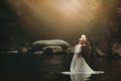 Jeune femme dans l'étang féerique photo stock