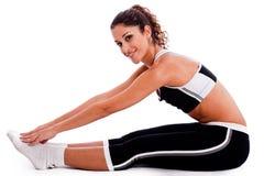 Jeune femme dans l'étirage d'équipements de forme physique Image stock