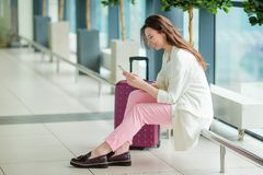 Jeune femme dans l'aéroport international avec son bagage et smartphone attendant son vol Photos stock