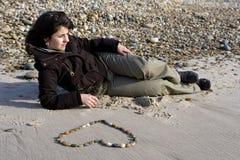 Jeune femme dans l'amour avec le coeur dessiné en sable Images libres de droits