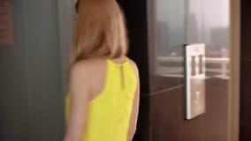 Jeune femme dans l'arrivée de attente d'ascenseur de robe jaune Entrant dans l'ascenseur les portes se ferment clips vidéos