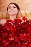 Jeune femme dans l'eau de bain de pétale rose. Photos libres de droits