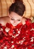 Jeune femme dans l'eau de bain de pétale rose. Image stock