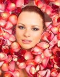 Jeune femme dans l'eau de bain de pétale rose Images stock