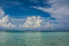 Jeune femme dans l'eau de turquoise sous le ciel nuageux image libre de droits