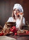 Jeune femme dans l'uniforme d'un chef mangeant des carottes image libre de droits