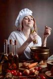 Jeune femme dans l'uniforme de chef avec de petites bouteilles d'huile végétale photo libre de droits