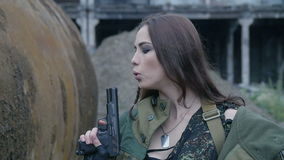Jeune femme dans l'uniforme militaire avec l'arme à feu banque de vidéos