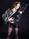 Jeune femme dans l'uniforme militaire avec le fusil d'assaut Image stock