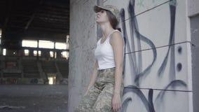 Jeune femme dans l'uniforme militaire se cachant de l'ennemi dans le bâtiment abandonné sale poussiéreux Fille mince courant jusq clips vidéos