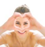 Jeune femme dans la baignoire regardant par les mains en forme de coeur Image libre de droits