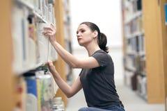 Jeune femme dans la bibliothèque Image libre de droits