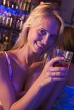 Jeune femme dans la boîte de nuit souriant à l'appareil-photo Photos libres de droits