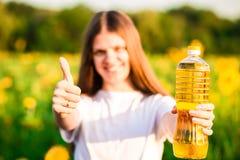 Jeune femme dans la bouteille se tenante blanche d'huile dans le domaine de tournesol images libres de droits