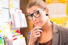 Jeune femme dans la boutique de loto jouant le billet Photos libres de droits